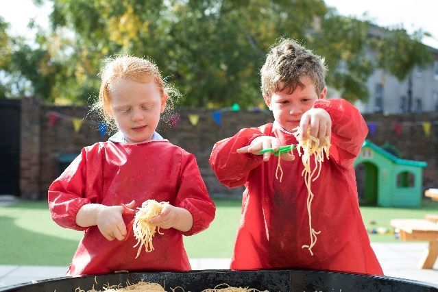 children cutting up spaghetti