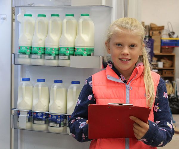 girl next to milk fridge holding clipboard